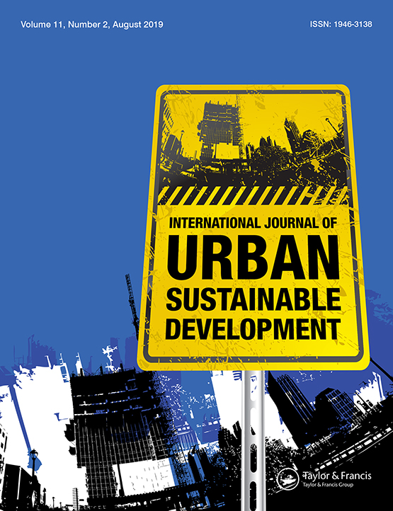 Journal cover - black title on yellow banner shaped like construction sign, blue background with artistic imagery of city buildings